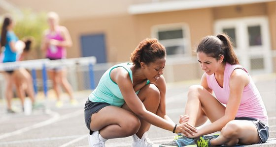 Two female runners on track, one helping the other who has a hurt ankle