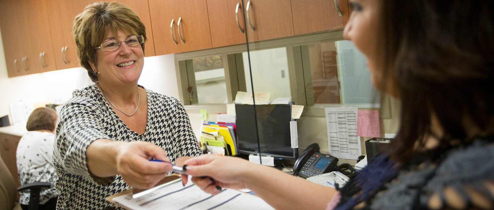 Smiling office assistant handing form to patient